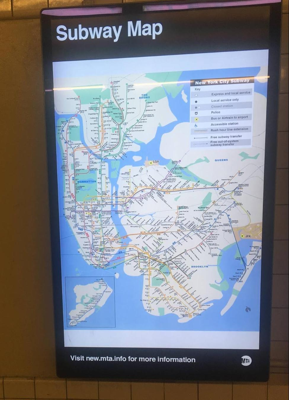 "A photograph of a TV in a subway station with the ""paper"" map displayed."